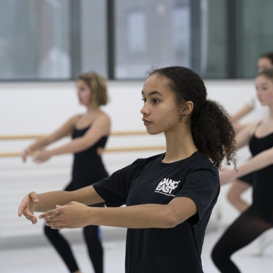 Student in ballet class with arms in a held position